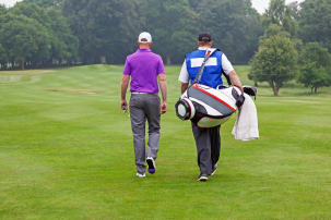 Caddy and golfer walking together