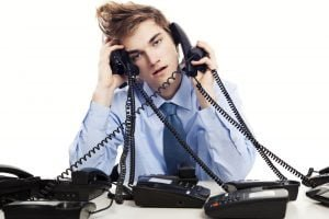 picture of a salesman with many phones making cold calls