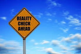 Road sign that says reality check ahead